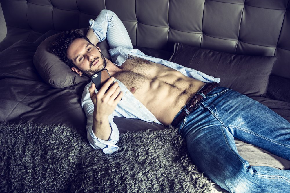 male with curly hair and unbuttoned shirt lying on a sofa and looking at his smartphone