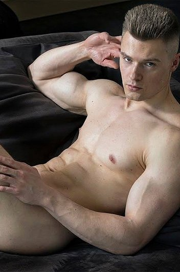 white male with short light brown hair and large biceps reclining on a bed