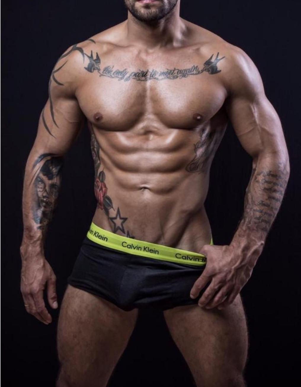 muscular mixed race man wearing a jock strap standing