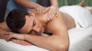 gay male massage in progress, a male is lying down and being massaged