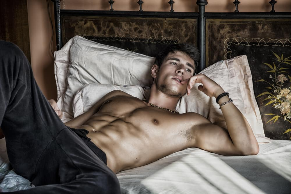 handsome gay masseur lying on a bed and waiting for a massage booking in his London flat