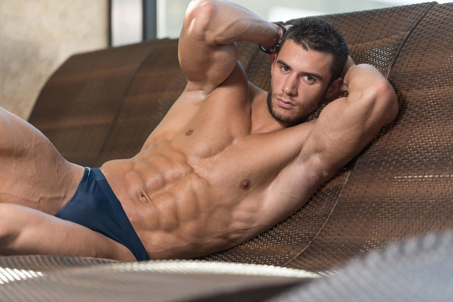 muscular male reclining on a sofa in black swimming trunks
