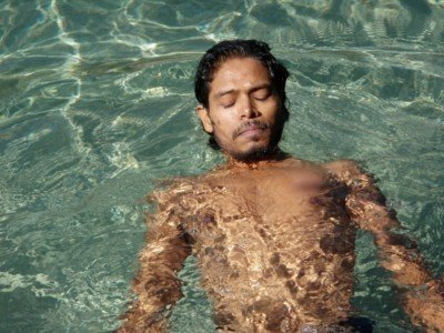 Body treatments for men: asian male in a swimming pool with eyes closed