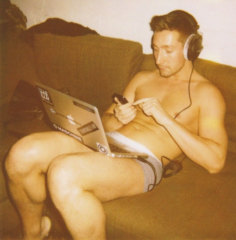 male sitting in his underwear, browsing on his phone