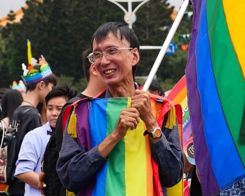 Activist celebrating gay marriage in Taiwan and waving a flag