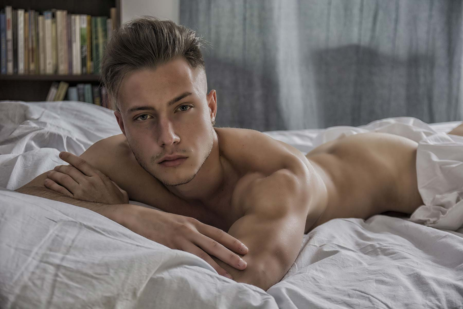 blond gay masseur lying on his stomach in his London flat