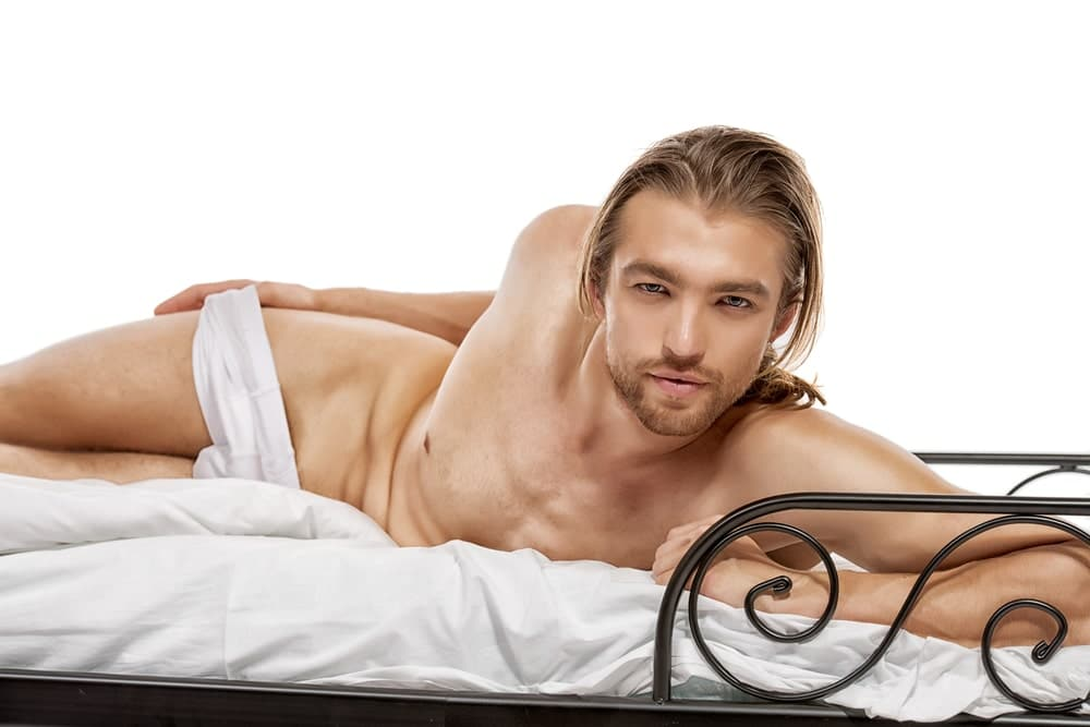 long-haired blond male lying on his side on a bed