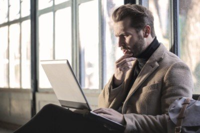 privacy issues: male looking at a laptop with a confused expression