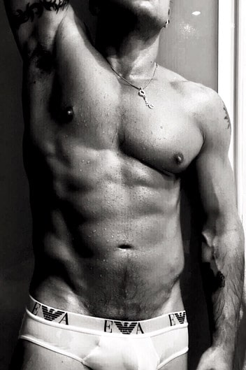 masseur danny : a greyscale photo of a muscular male standing in white armani briefs with his arms raised