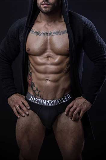 masseur ethan : muscular latin male wearing an unzipped black hoodie and black briefs