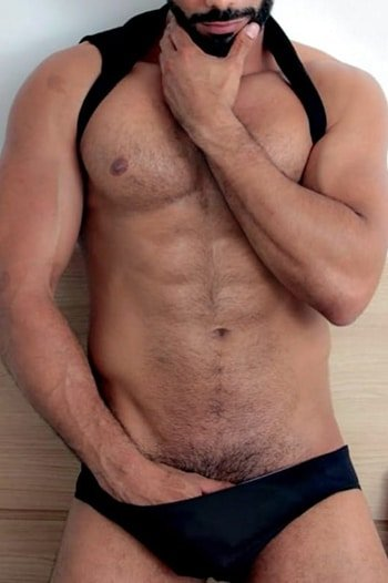 masseur jordan : muscular latin male with a black beard standing with his hand in black briefs