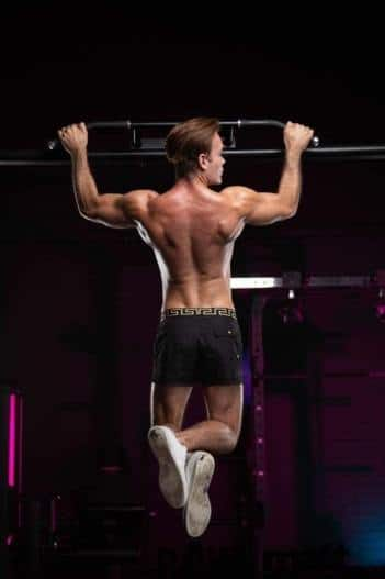 masseur luis : muscular white male with brown hair doing a pull up, wearing black shorts and white sneakers