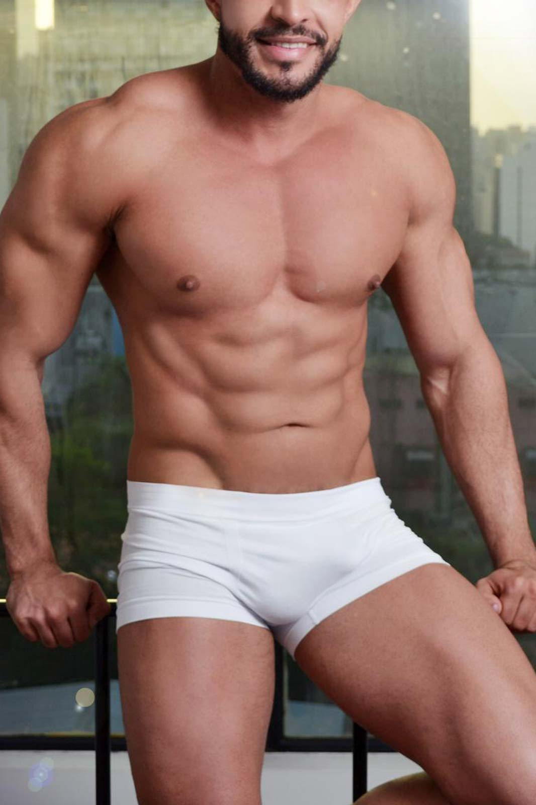 masseur ricardo : muscular latin male wearing white trunks, sitting down and smiling