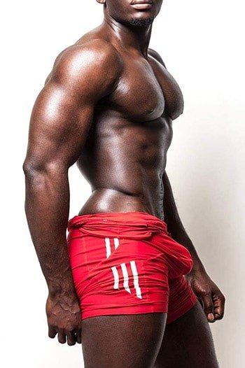 masseur william : muscular black male standing sideways, wearing red shorts with white stripes