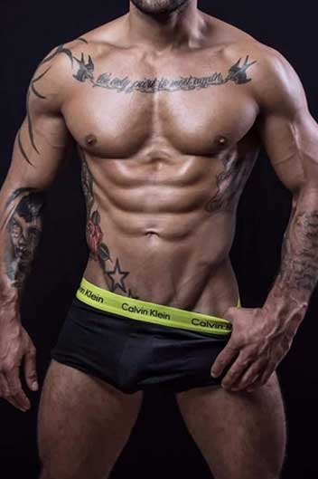 masseur ethan : muscular latin male with tattoos wearing black trunks