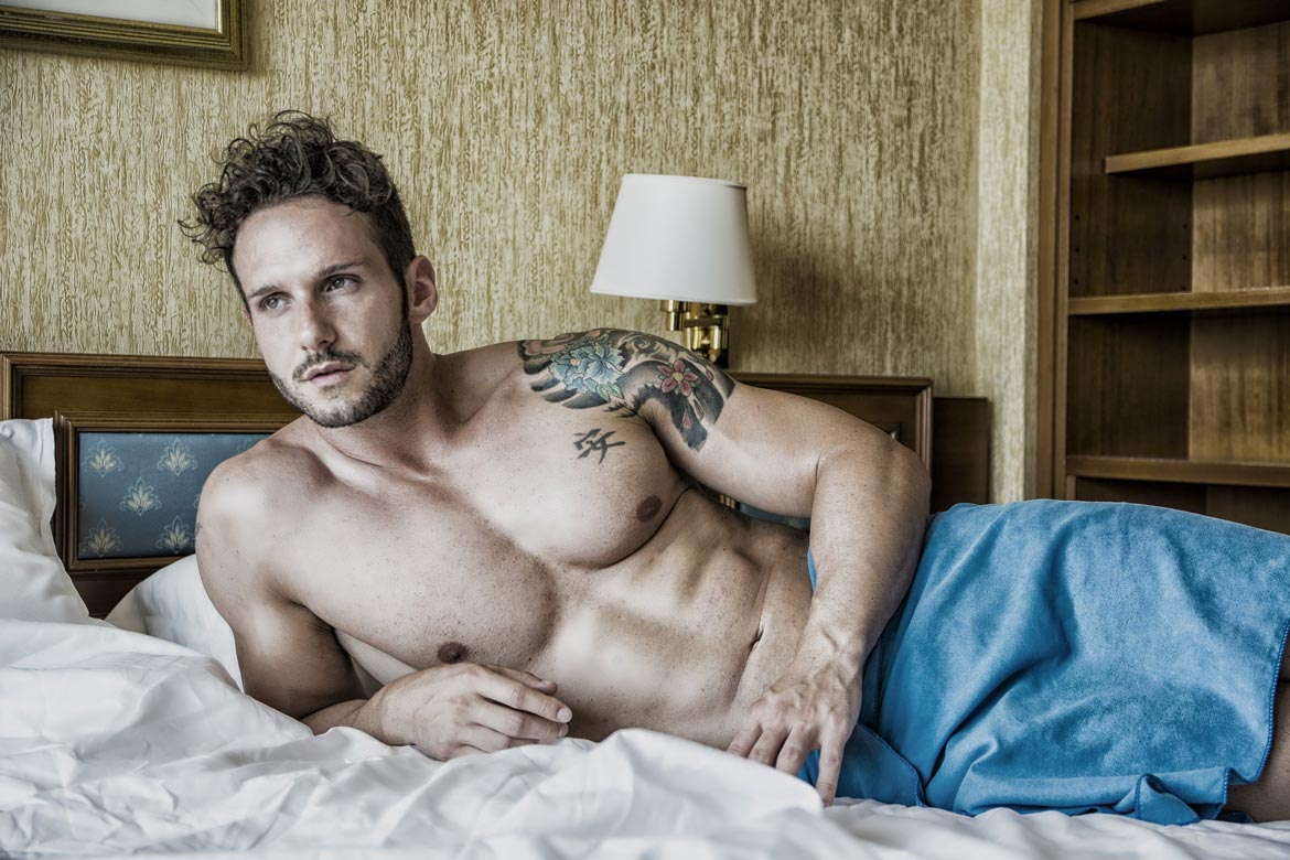 handsome masseur lying on his side, waiting for a sensual gay massage in London