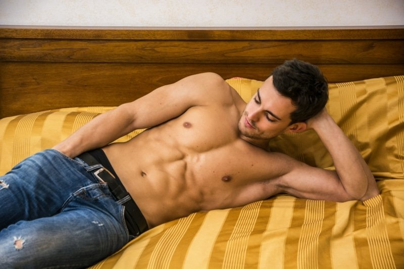 male lying on bed, talking during a male to male massage in london