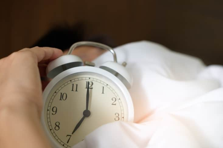 male in bed holding an alarm clock