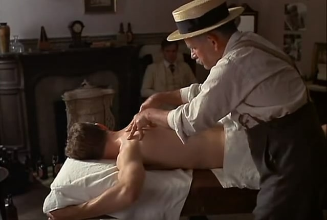 older masseur in a shirt, braces and a hat massages a young male as another looks on