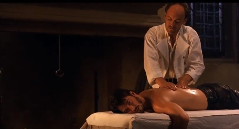 older male in a white shirt massages another male who is lying down