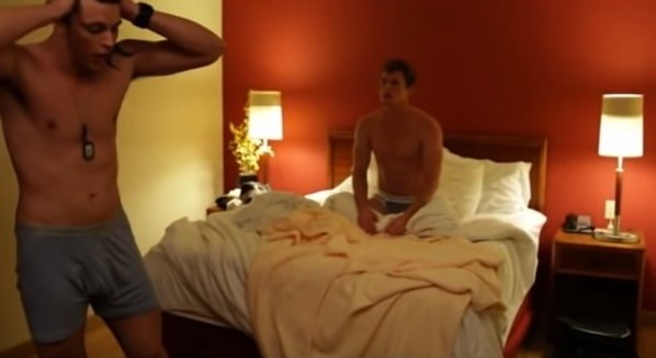 young male standing in despair as another looks on from the bed