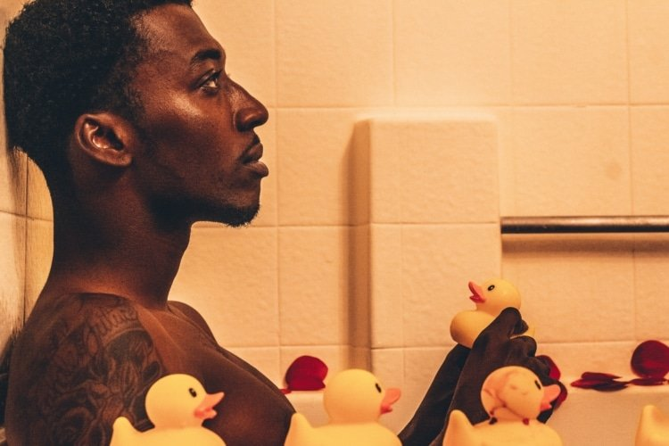 man sitting in a bathtub surrounded by rubber ducks