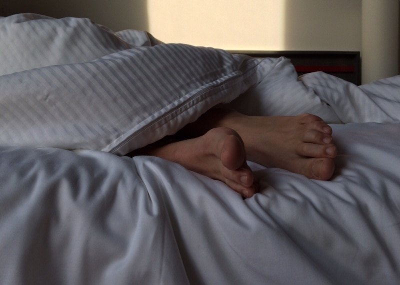 male feet poking from under a duvet