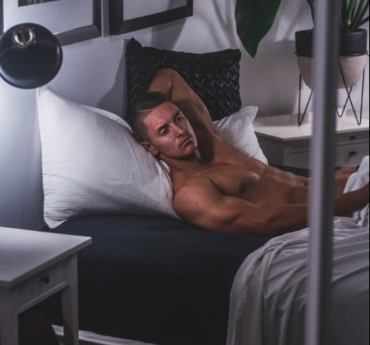 shirtless male lying in bed