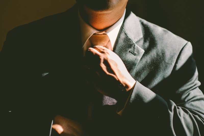 businessman in a suit adjusting his tie