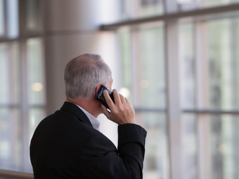 a white male with grey hair talking on the phone