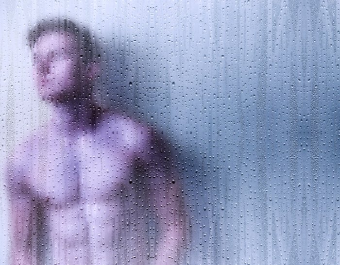 male standing behind a wet glass