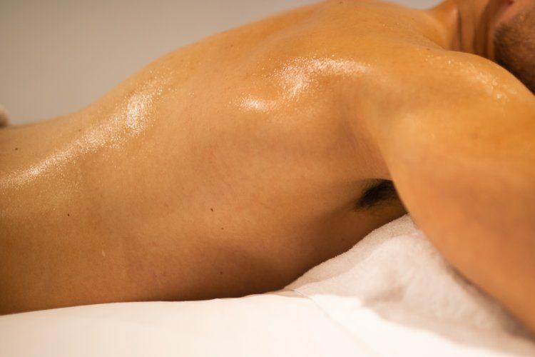 oiled male body lying down