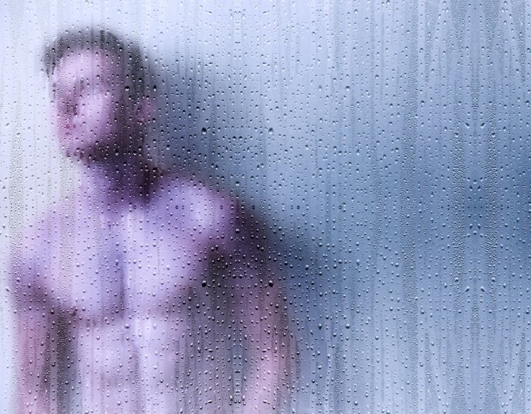muscular male standing in a shower
